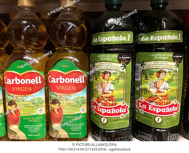 12 March 2019, Spain, Madrid: Olive oil bottles stand on a shelf in a supermarket in Madrid. Olive oil is considered one of the secret recipes of the...