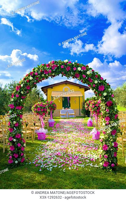 The wedding venue with a flower arch and a petal path