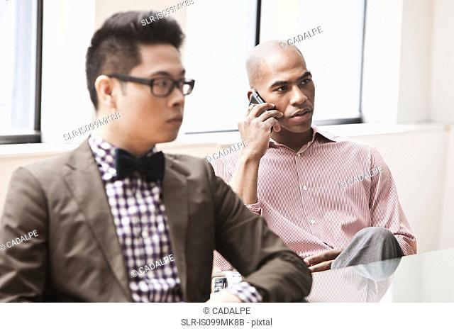 Two businessmen, one on the phone