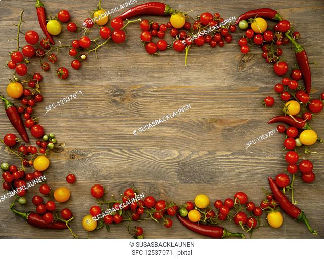 Various different types of tomatoes and chilli peppers on a wooden board