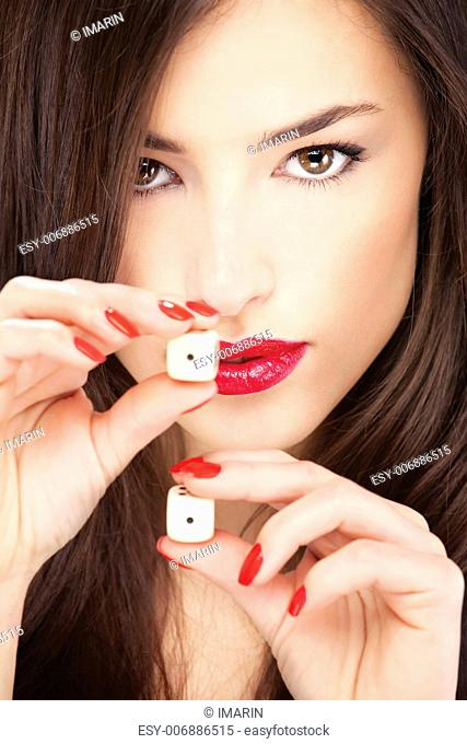 Close up of a pretty young woman holding dices