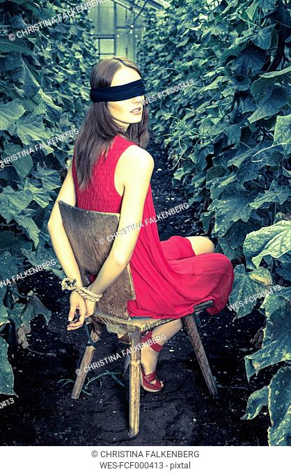 Constrained and blindfolded young woman in greenhouse