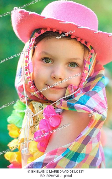 Portrait of girl wearing pink cowboy hat in garden