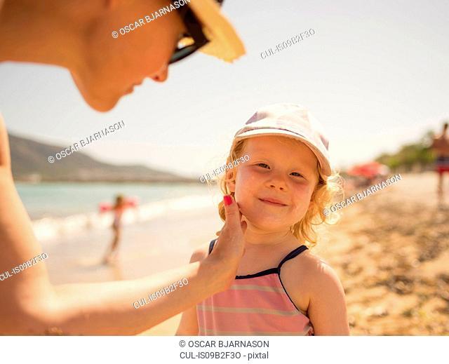Woman applying suncream to daughter's face on beach, Altea, Alicante Province, Spain