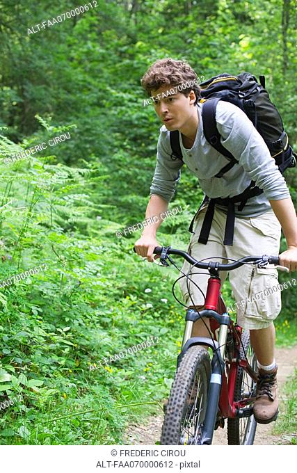 Man riding bicycle in woods