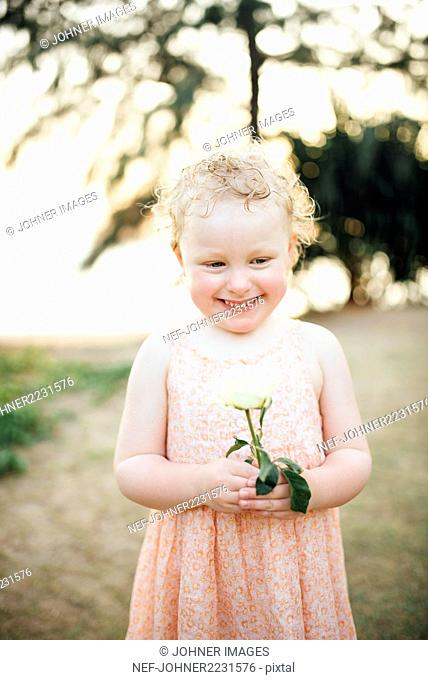 Portrait of smiling girl with white rose