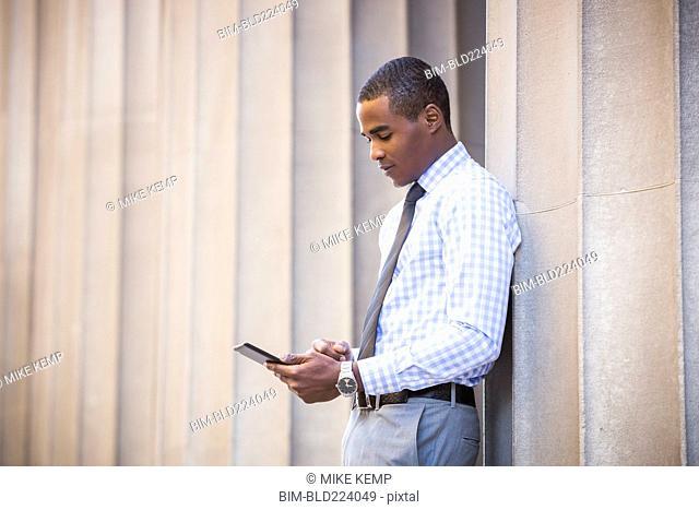 Black businessman leaning on wall using digital tablet