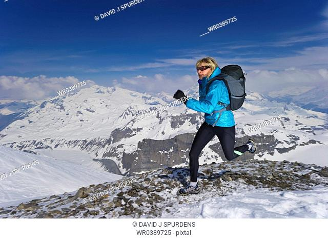 Runner jogging along rocky snow covered mountain path