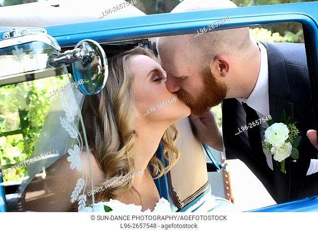 bride getting out of blue car & groom kissing her - shot through the window