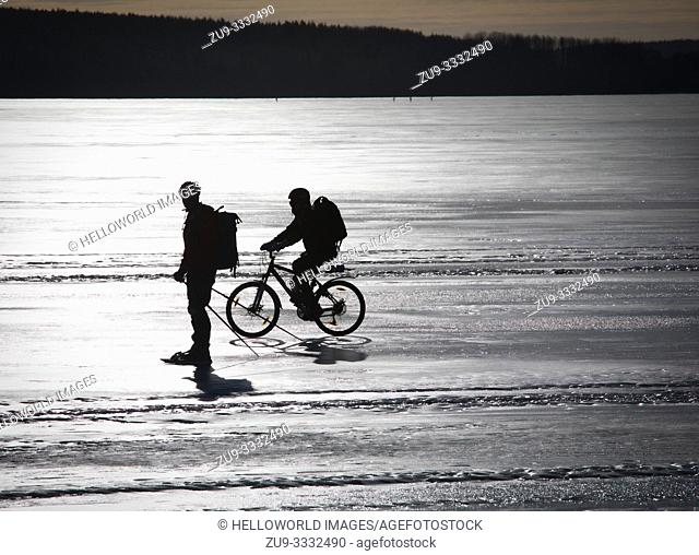 Cyclist and long distance ice skater silhouetted on frozen Lake Malaren
