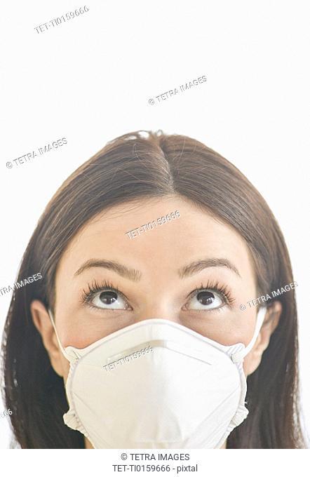 Studio portrait of woman wearing flu mask