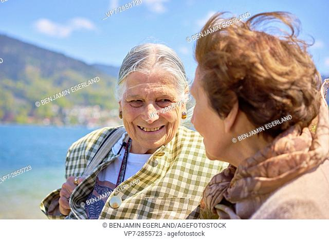 Happy senior woman enjoying togetherness with old friend at lake Tegernsee in Bavaria, Germany