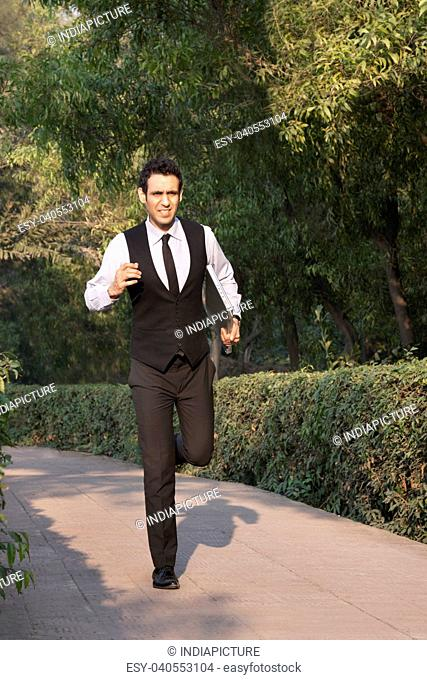 Businessman with laptop running in a park , INDIA , DELHI