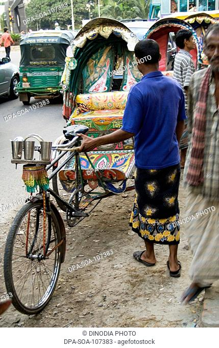 Cycle  Rickshaw Rider with Vehicle on street at Dhaka ; Bangladesh