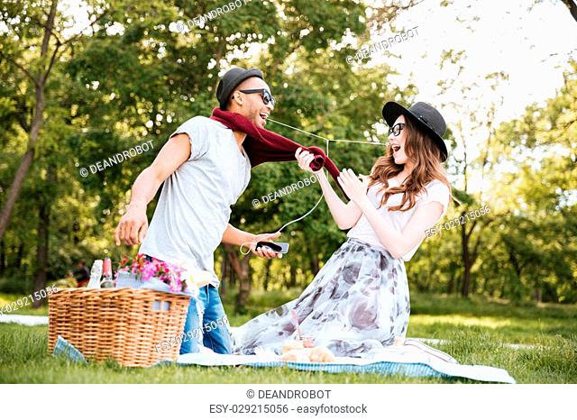 Happy young couple having fun and listening to music from smartphone on picnic