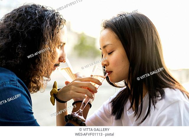 Young couple drinking champagne at the riverside