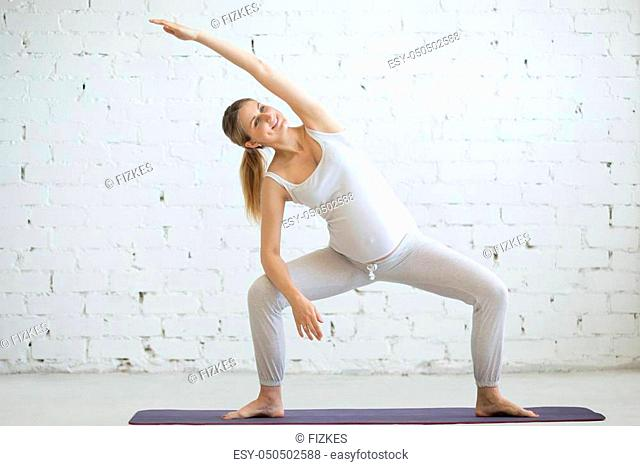 Pregnancy Yoga, Fitness concept. Portrait of beautiful young pregnant yoga model working out indoor. Pregnant happy fitness person enjoy yoga practice at home