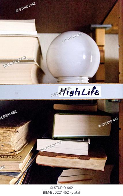 Close up of light bulb on shelf with books