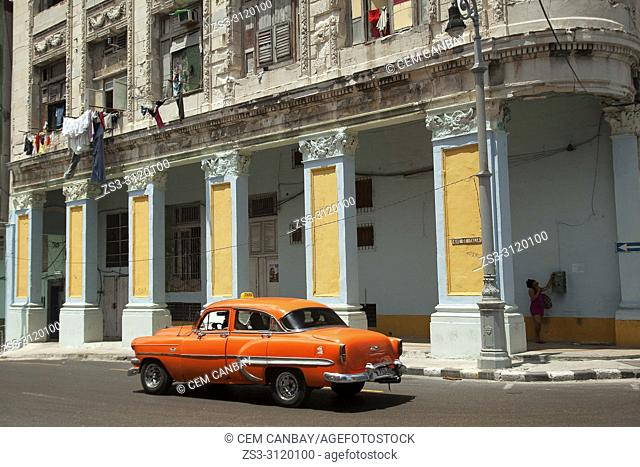 Old American cars used as taxi in front of the colonial buildings in Central Havana, La Habana, Cuba, West Indies, Central America