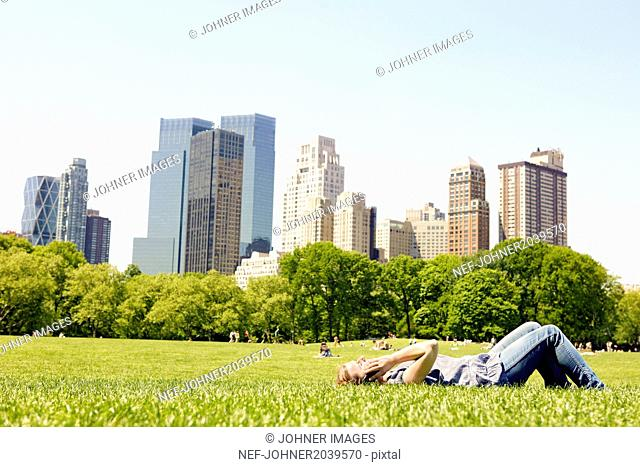 Woman in Central Park with Manhattan skyline, New York City, USA