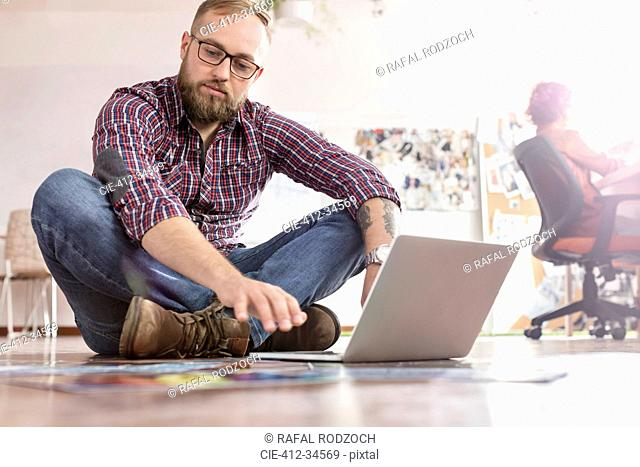Male design professional reviewing proofs at laptop on office floor