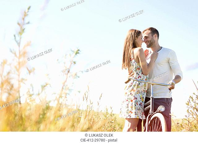 Affectionate young couple with bike hugging in sunny rural field