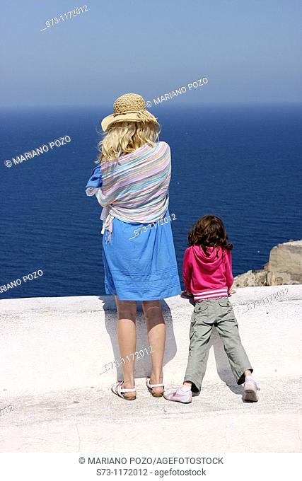 Woman and daughter watching the sea, Santorini, Oia, Cyclades Islands, Greece
