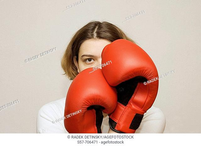 Young woman wearing red boxing gloves
