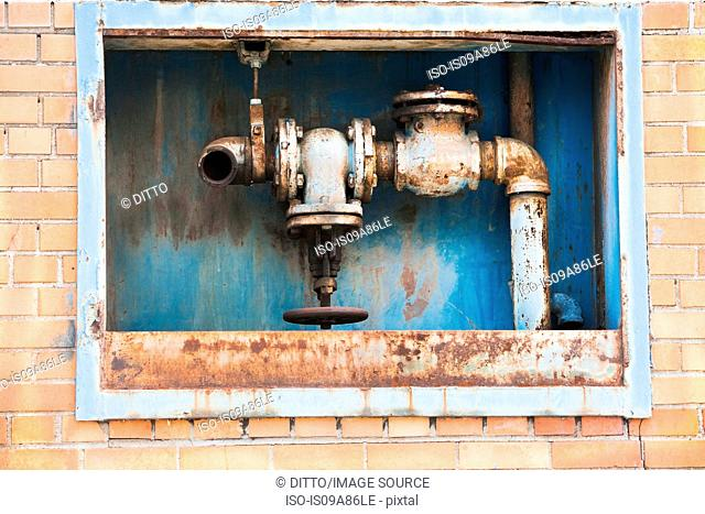Rusting pipes inside red brick wall