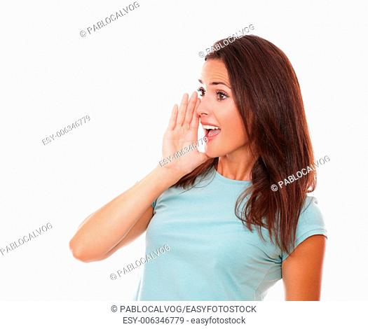Portrait of 30s latin female on blue t-shirt screaming to her right on isolated white background - copyspace