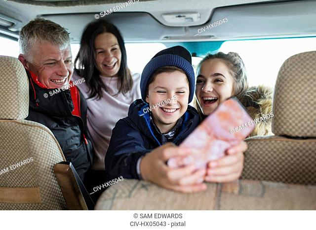 Happy family with smart phone in motor home