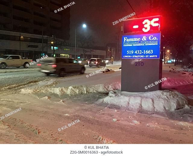 Street covered in fresh snow at temperature below zero, evening traffic, Ontario, Canada