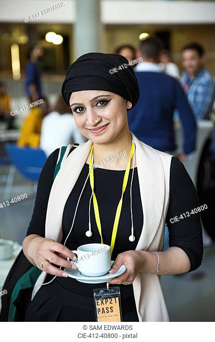 Portrait smiling, confident businesswoman in headscarf drinking coffee at conference