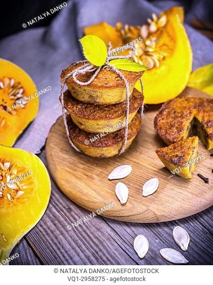 cupcakes with pumpkin on a round wooden board, next to pieces of fresh pumpkin