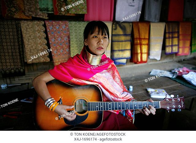 A Longneck woman plays a guitar Approximately 300 Burmese refugees in Thailand are members of the indigenous group known as the Longnecks The largest of the...