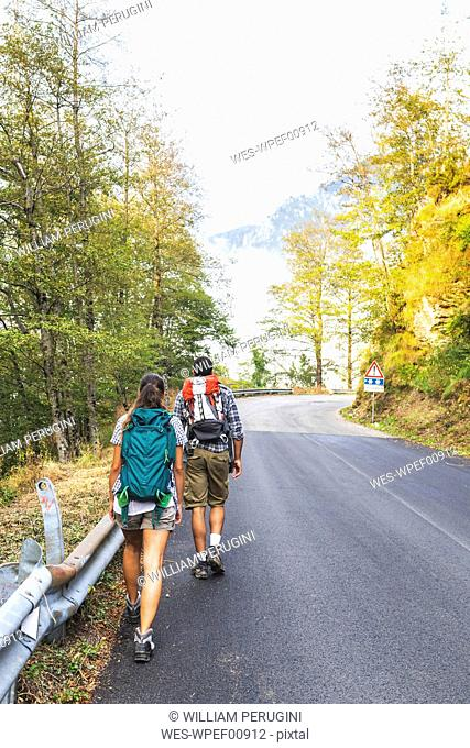 Italy, Massa, rear view of young couple walking on asphalt road in the Alpi Apuane mountains
