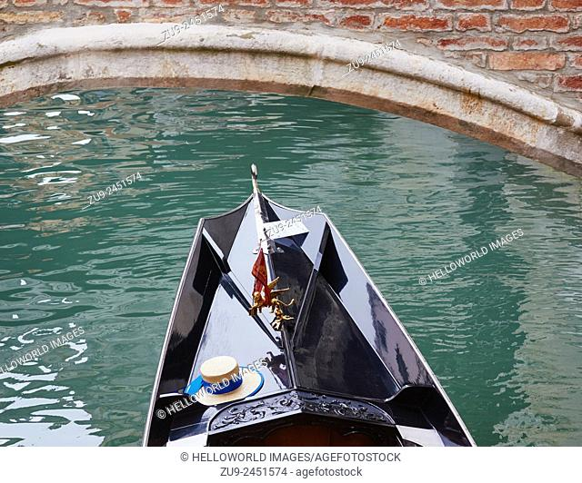 Gondola passing under a bridge with the Venetian flag and straw hat of the gondolier, Venice, Veneto, Italy, Europe