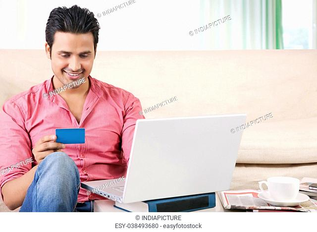 Young man shopping online with credit card at home on laptop