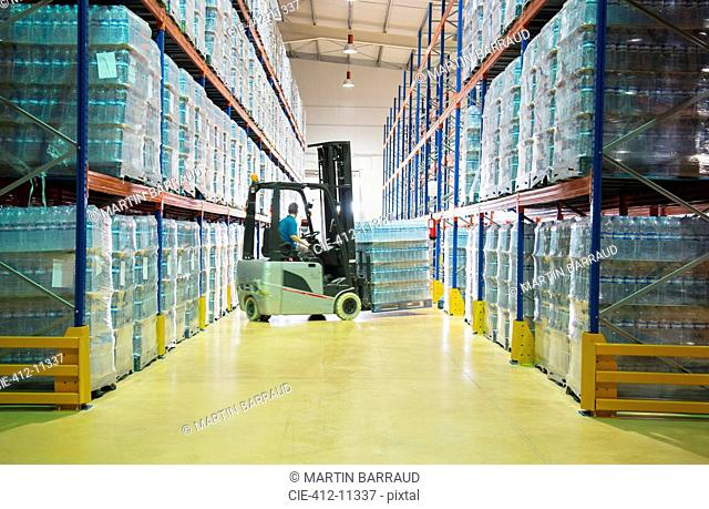 Worker moving pallets with forklift in warehouse