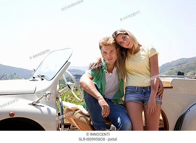 Young couple by convertible car looking at camera