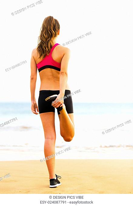Young Attractive Fitness Woman Stretching on the Beach, Working Out. Healthy Active Outdoor Lifestyle