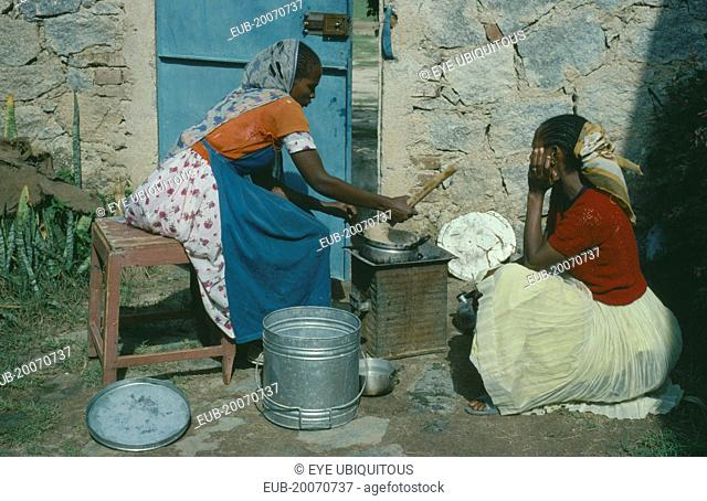 Women cooking over charcoal