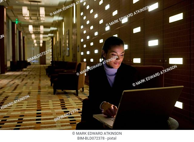 African businesswoman working on laptop late in lobby