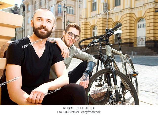 Attractive hipster men are sitting near their bicycles on the street. They are smiling and looking at the camera