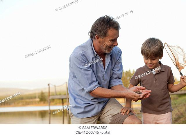 Smiling grandfather and grandson fishing at lakeside