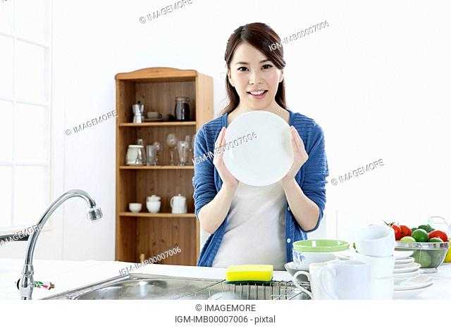 Young woman holding plate and smiling at the camera