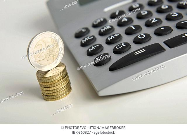 Stacked Euro coins next to a calculator