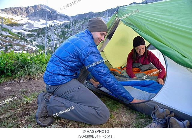 Couple putting sleeping bag in tent at Fault Lake, Selkirk Mountains, Idaho