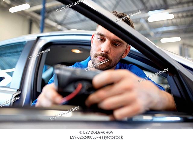 service, repair, maintenance and people concept - mechanic man with automotive diagnostic scanner checking car system at workshop