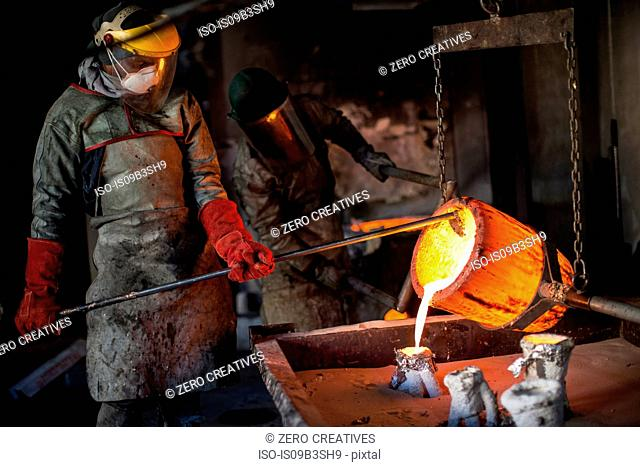 Metalworkers working in foundry, pouring molten bronze